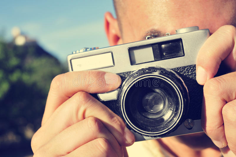Young man taking a picture with an old camera. Closeup of a young man taking a picture with an old camera outdoors stock image