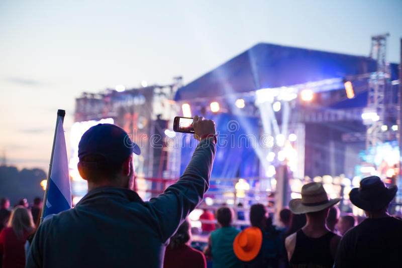 Young man taking pictures rock concert on phone stock photos