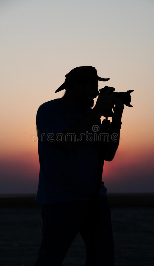 Young Man Taking Pictures At Sunset Stock Photo