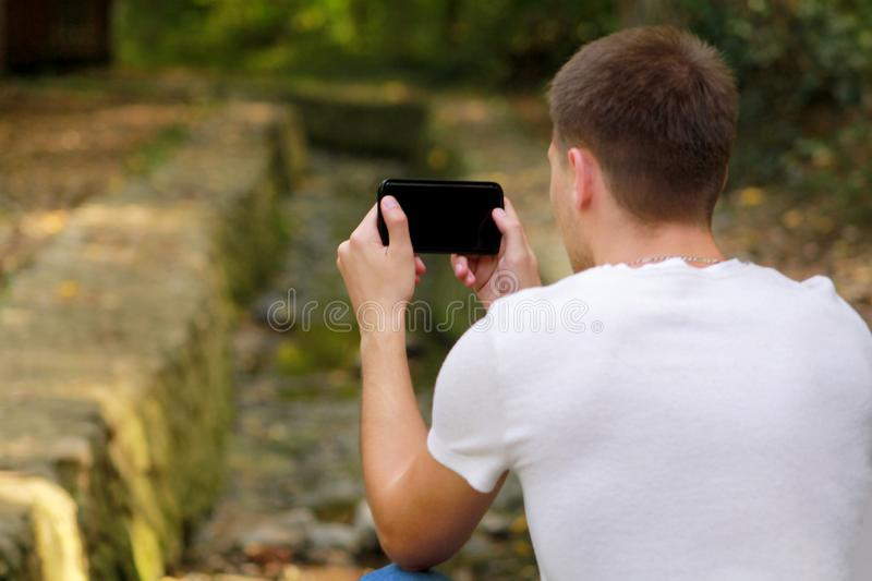 Young man taking pictures using camera his smart phone in nature, park and forest, a small river, a stream. stock images