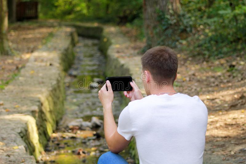 Young man taking pictures using camera his smart phone in nature, park and forest, a small river, a stream. royalty free stock photography