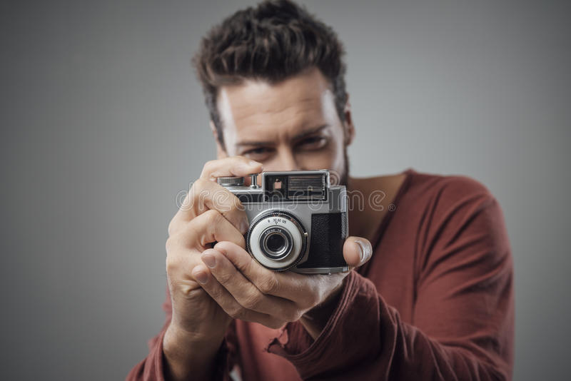 Young man taking pictures with a vintage camera. Young man taking pictures with an old vintage camera royalty free stock photography