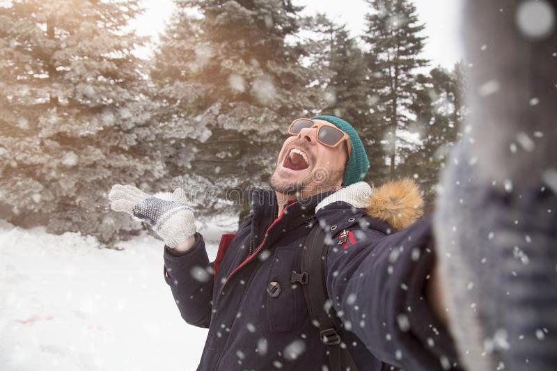 Young fashionable man taking self portrait in forest. Winter scene stock images