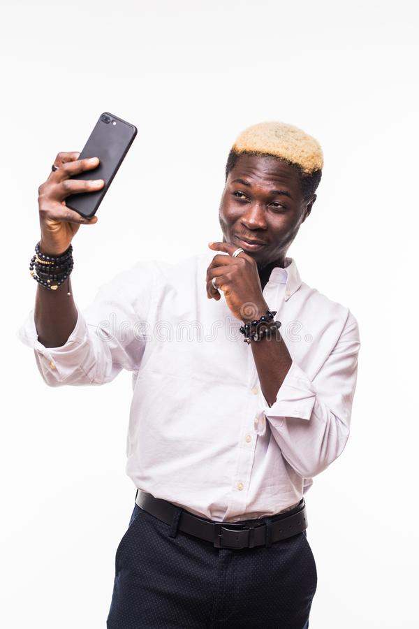 Young handsome african man taking a selfie with a cell phone, isolated on white. Young man taking a selfie with a cell phone, isolated on white stock images