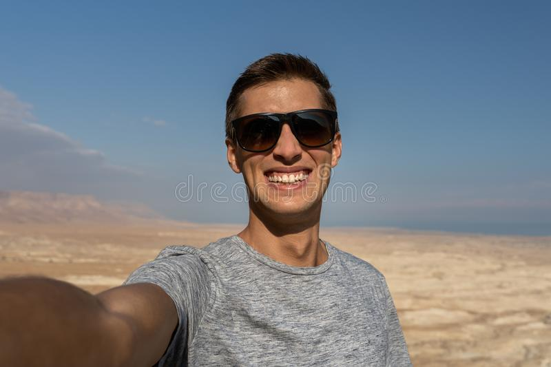 Young man taking a selfie in the desert of israel stock photo