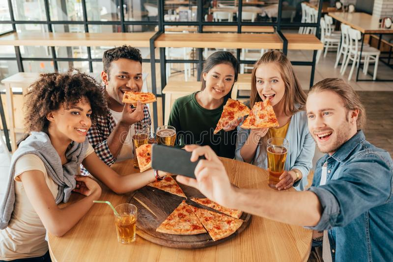 Young man taking selfie with multiethnic friends having pizza royalty free stock photos