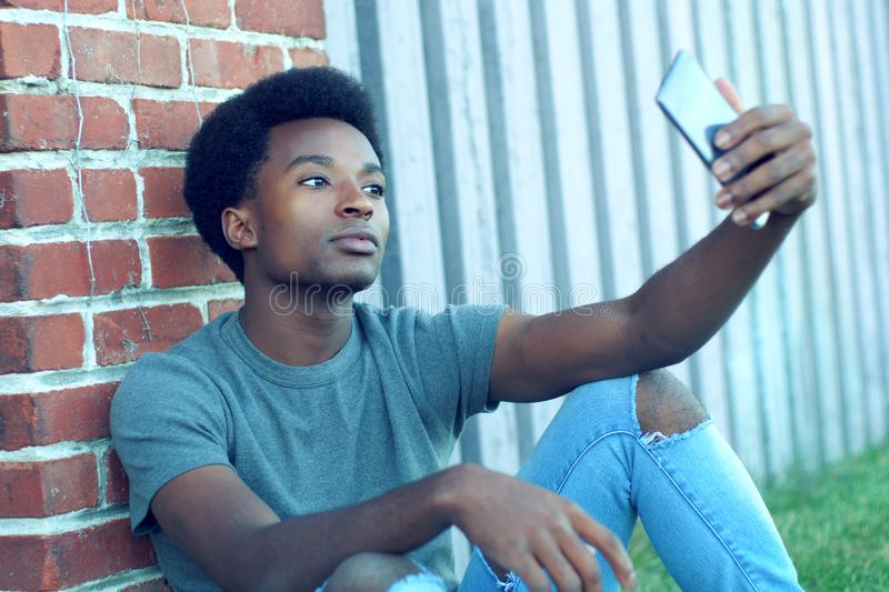 Young man taking selfie outside sitting in grass wearing jeans smartphone pic portrait technology royalty free stock photo