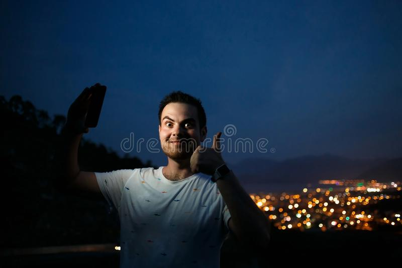 Young man taking selfie on top of the hill observing the night city view. Good light from screen. Thumbs up gesture stock image