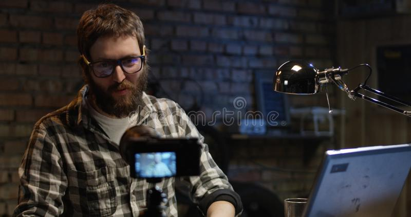 Young man talking on camera in a workshop royalty free stock photo