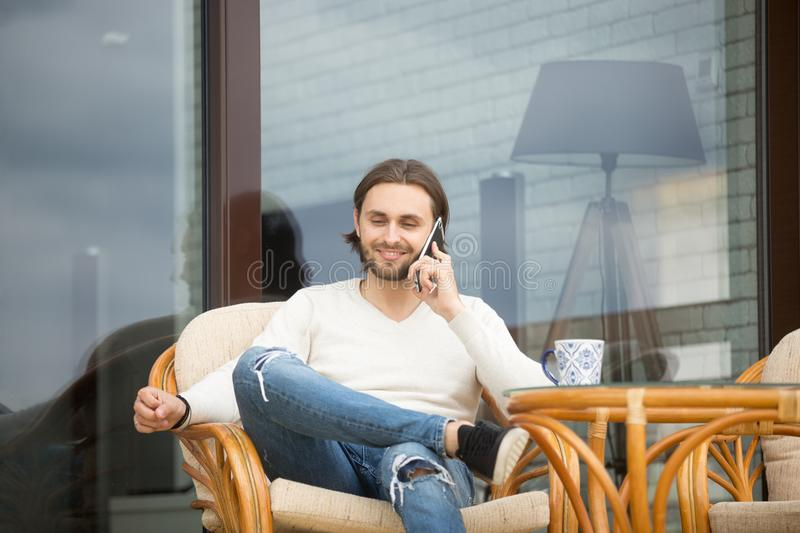 Young man talking by cell sitting on house terrace chair royalty free stock photos