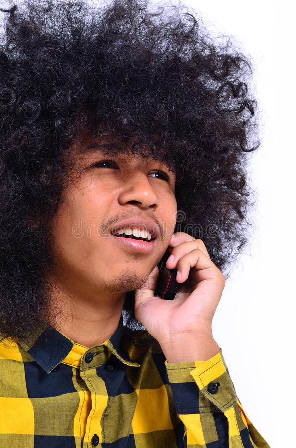 Young man talking on the cellphone. Close up of Long-haired young man talking on the cellphone royalty free stock photos