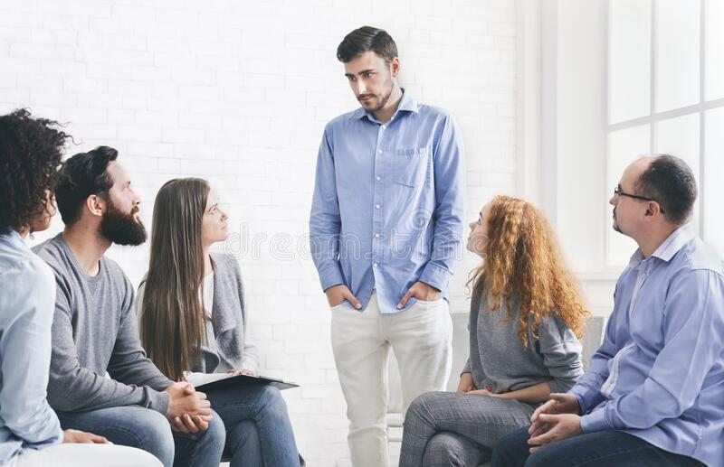 Young man talking about his problems during group therapy royalty free stock photo