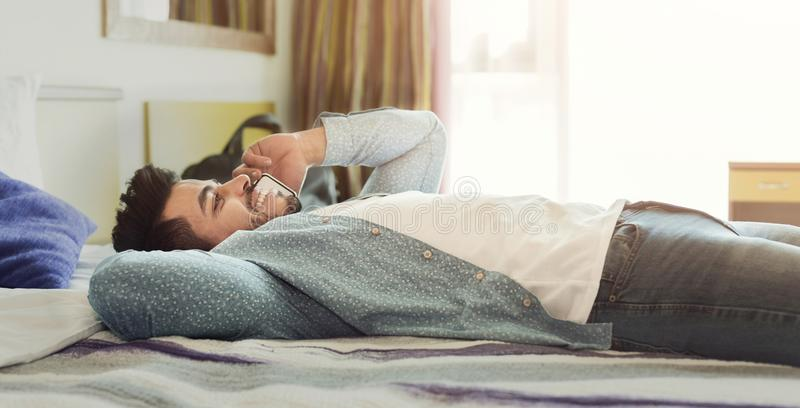 Young man talking on mobile phone while relaxing in bed royalty free stock image