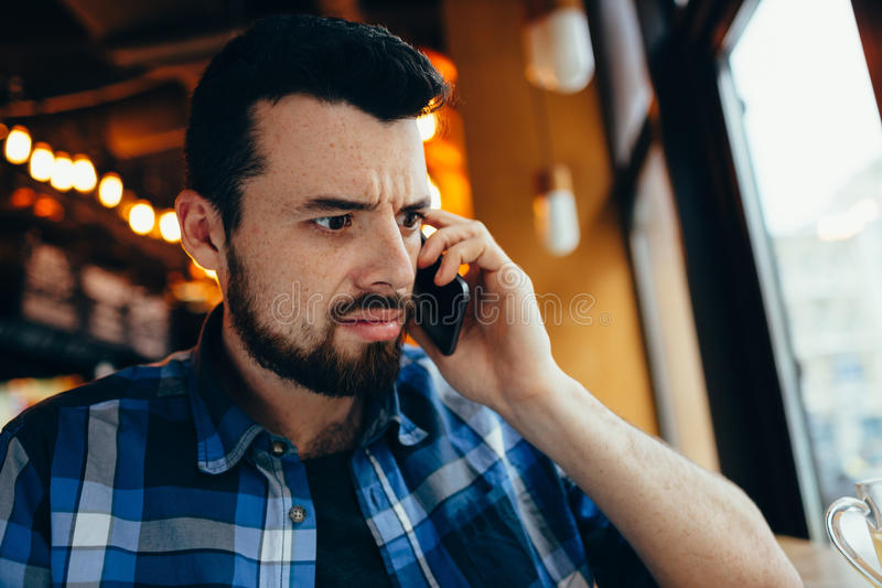 Young man talking on the phone in cafe stock image