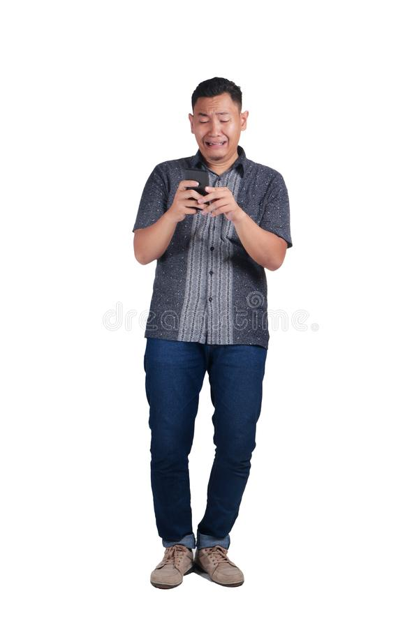 Young Man Talking on Phone, Cried Worried Expression. Young Asian man wearing blue jeans and batik shirt with an Expression of worried, cried, scared. Isolated royalty free stock images