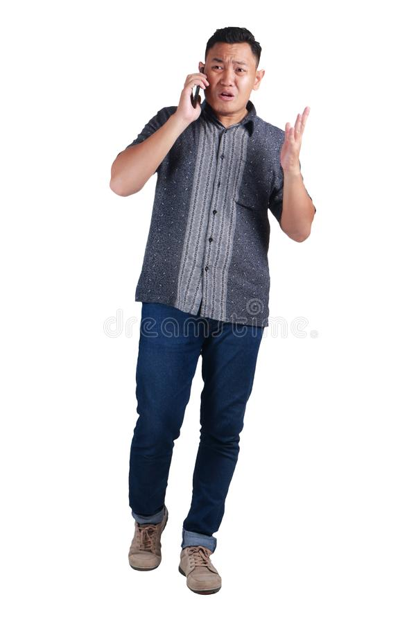 Young Man Talking at Phone, Cried Worried Expression. Young Asian man wearing blue jeans and batik shirt talking at phone, cried and worried expression. Isolated stock image