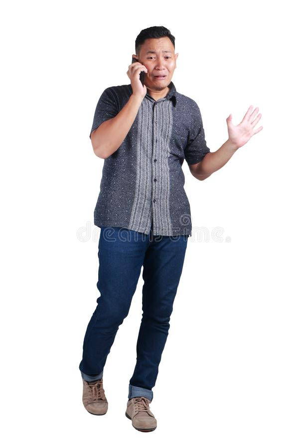 Young Man Talking at Phone, Cried Worried Expression. Young Asian man wearing blue jeans and batik shirt talking at phone, cried and worried expression. Isolated stock images