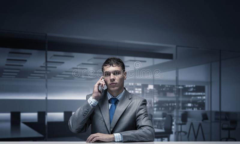 Young man talking on phone and looking at camera royalty free stock image