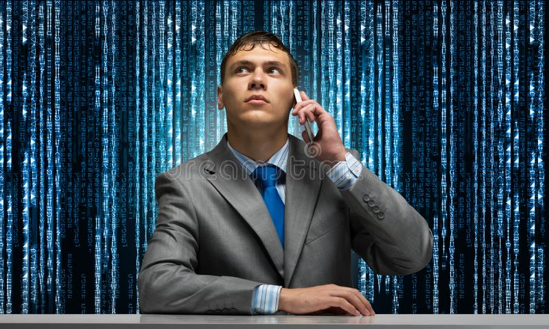 Young man talking on phone and looking upward. Businessman sitting at desk on background abstract binary code chain. Portrait of guy wears business suit and stock photos