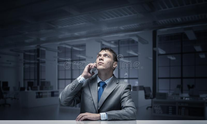 Young man talking on phone and looking upward. stock photos