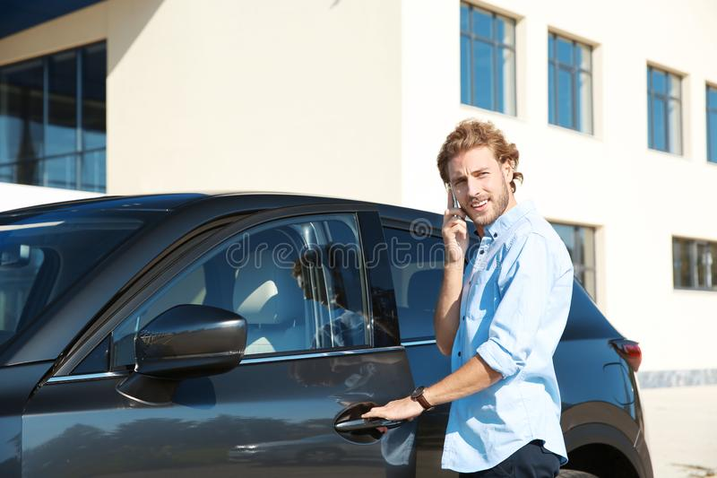Young man talking on phone while opening car door royalty free stock image