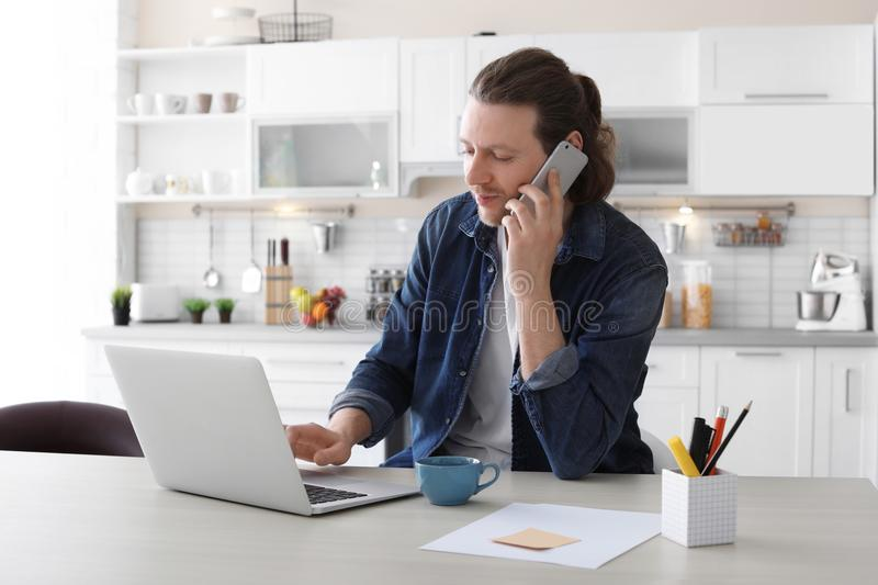 Young man talking on phone while working with laptop royalty free stock photos
