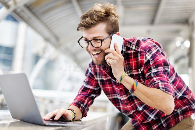 Young Man Talking Smartphone Browsing Laptop Concept stock photos