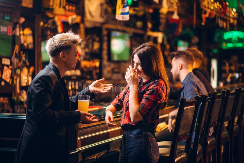 Young man talks with woman at the bar counter royalty free stock images