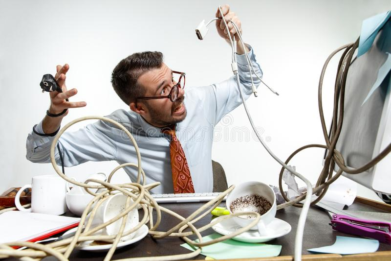 Young man tangled in wires on the workplace royalty free stock images