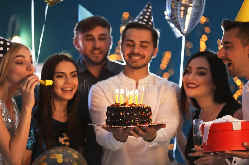 Young man with tasty cake and his friends at birthday party in club stock image