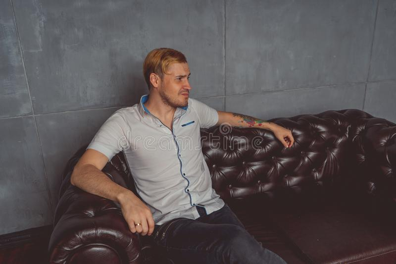 A young man with a tattoo on his hand posing on a leather couch. street style clothes: white shirt and black jeans. short hair and stock photo