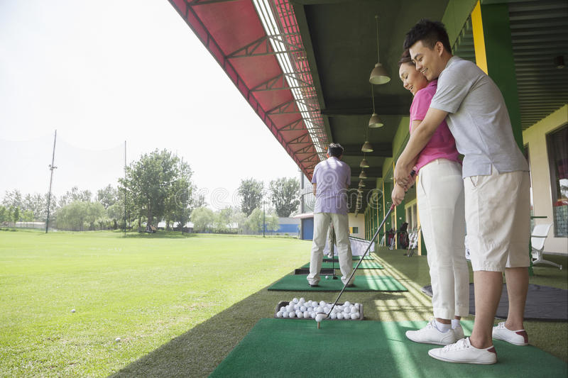Young man teaching his girlfriend how to hit golf balls, arm around, side view stock photos