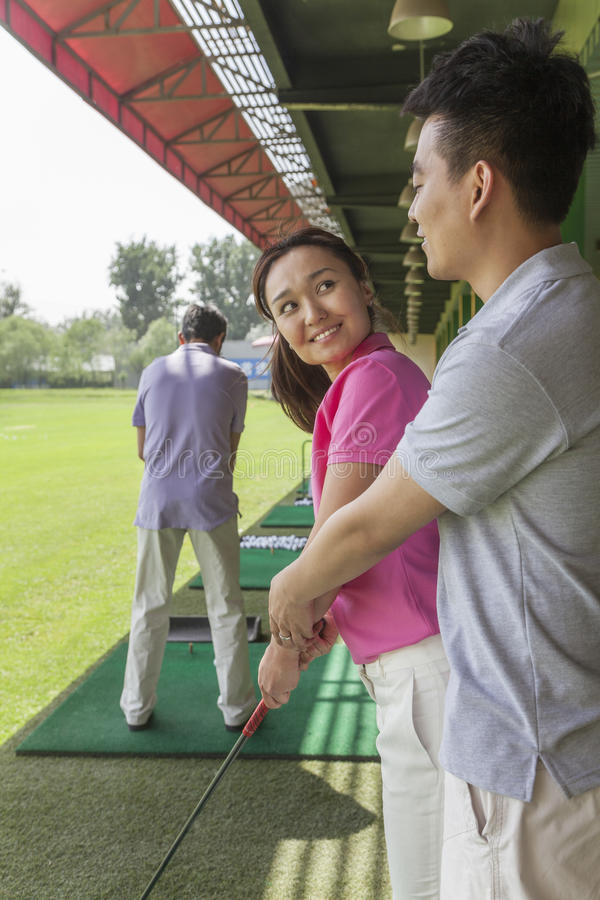 Young man teaching his girlfriend how to hit golf balls, arm around, side view royalty free stock photos