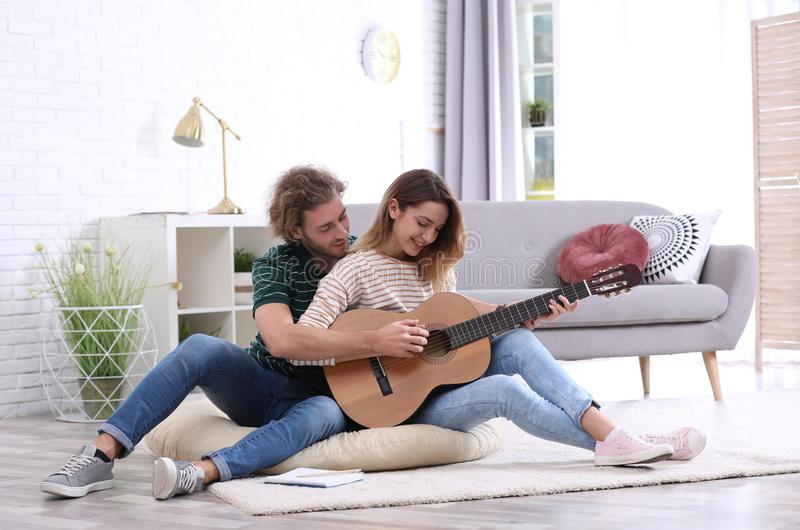 Young man teaching his girlfriend to play acoustic guitar. Young men teaching his girlfriend to play acoustic guitar in living room stock image
