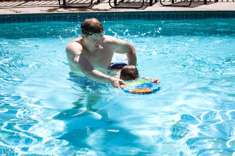 Young man teaching little boy to swim royalty free stock images