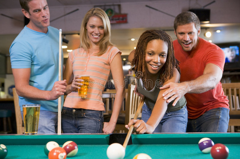 Young man teaching a young woman to play pool stock images