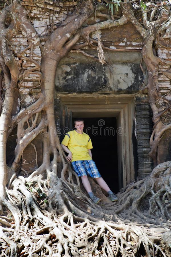 Young man, the teenager at an entrance to the destroyed covered with roots of trees temple Prasat Chrap in the Koh Ker temple comp royalty free stock photo