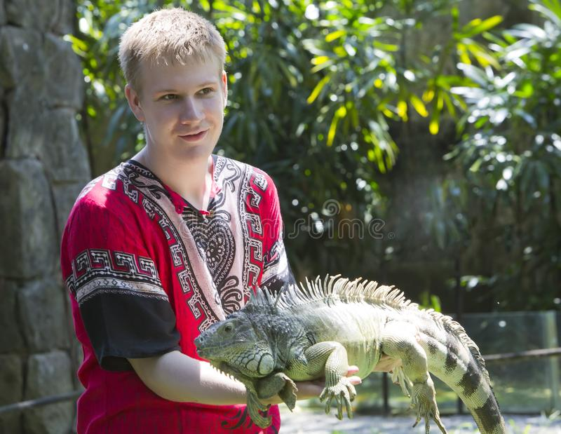 The young man, the teenager holds an iguana on hands royalty free stock photo