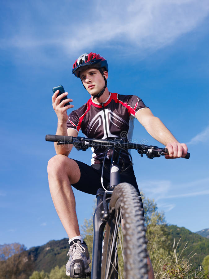 Young man with telephone riding mountain bike. Sports activity: young adult cyclist riding mountain bike and text messaging on cellphone. Vertical shape, low royalty free stock images