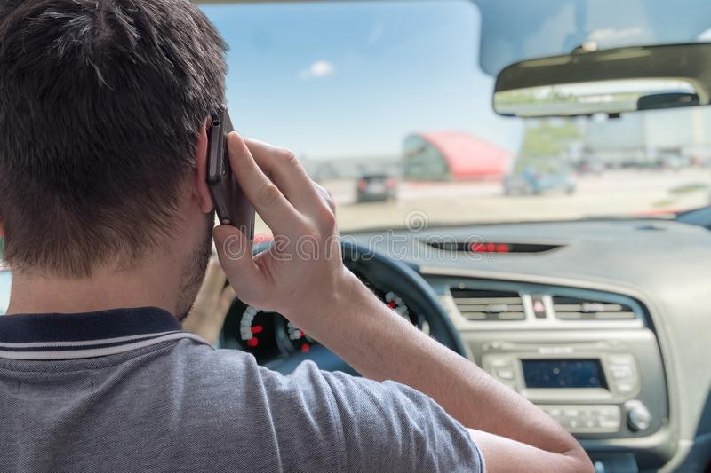 Young man is telephoning in car with smartphone stock photos