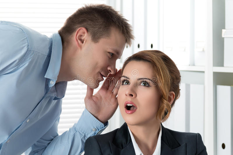 Young man telling gossips to his woman colleague. Young men telling gossips to his women colleague at the office. Intrigues and wasting time concept royalty free stock photo