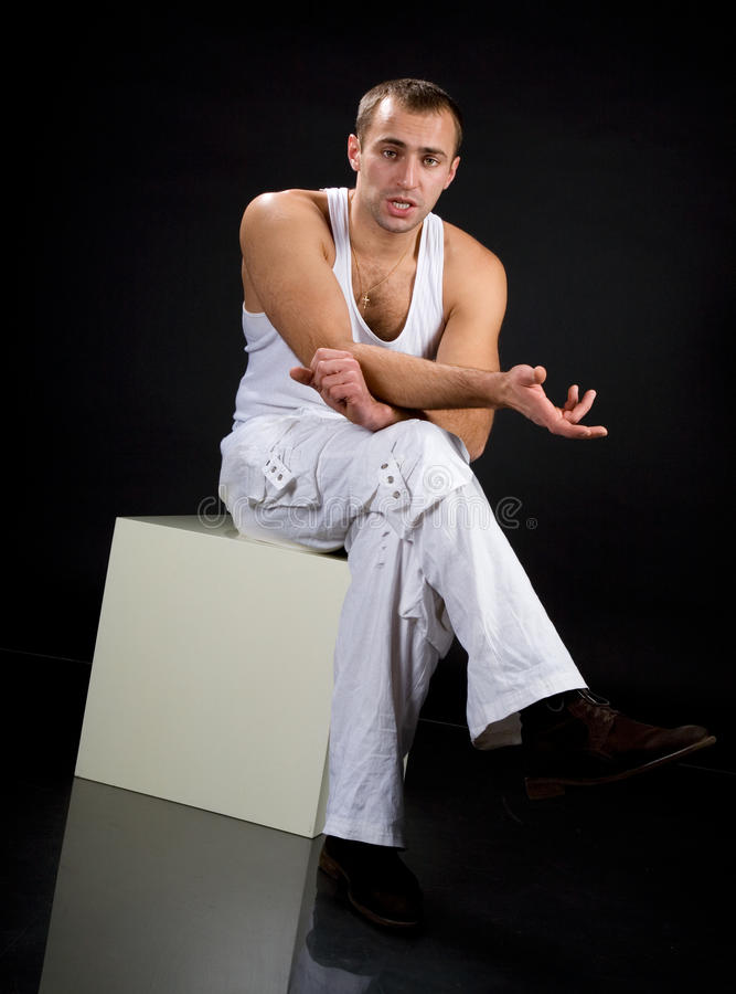 Young man tells. His interlocutor that is sitting on a white cube royalty free stock photos