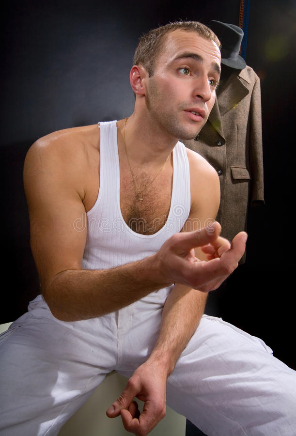 Young man tells. His interlocutor that is sitting on a white cube royalty free stock photography