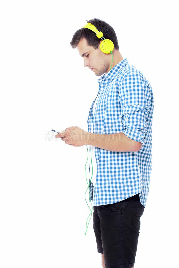 Young man texting on his phone and listening to music. Isolated on white background. Copy space. Mock up. Student chatting royalty free stock photos