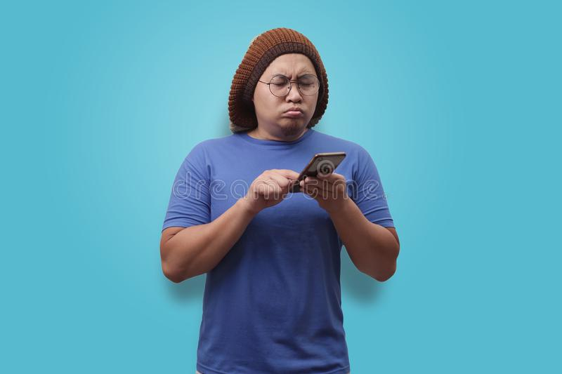 Young Man Texting Reading Chatting on His Phone, Confused Expression royalty free stock image