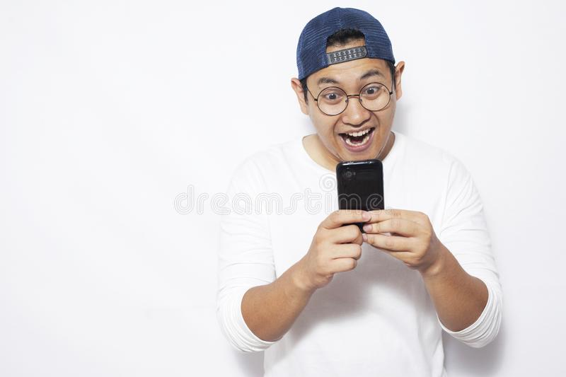 Young Man Texting Reading Chatting on His Phone, Smiling Happy royalty free stock image