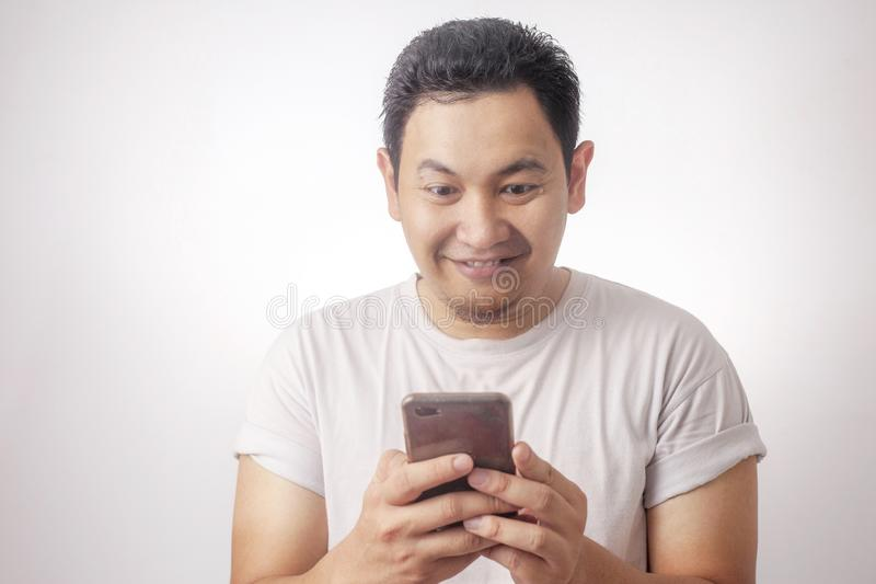 Young Man Texting Reading Chatting on His Phone, Smiling Happy royalty free stock photos