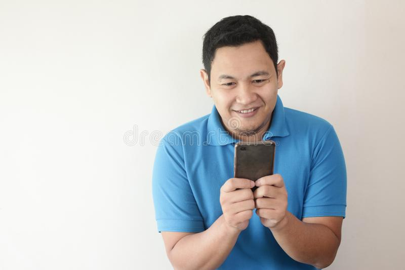Young Man Texting Reading Chatting on His Phone, Smiling Happy stock photo