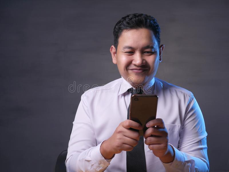 Young Man Texting Reading Chatting on His Phone, Smiling Happy royalty free stock images