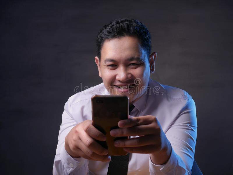 Young Man Texting Reading Chatting on His Phone, Smiling Happy royalty free stock photography